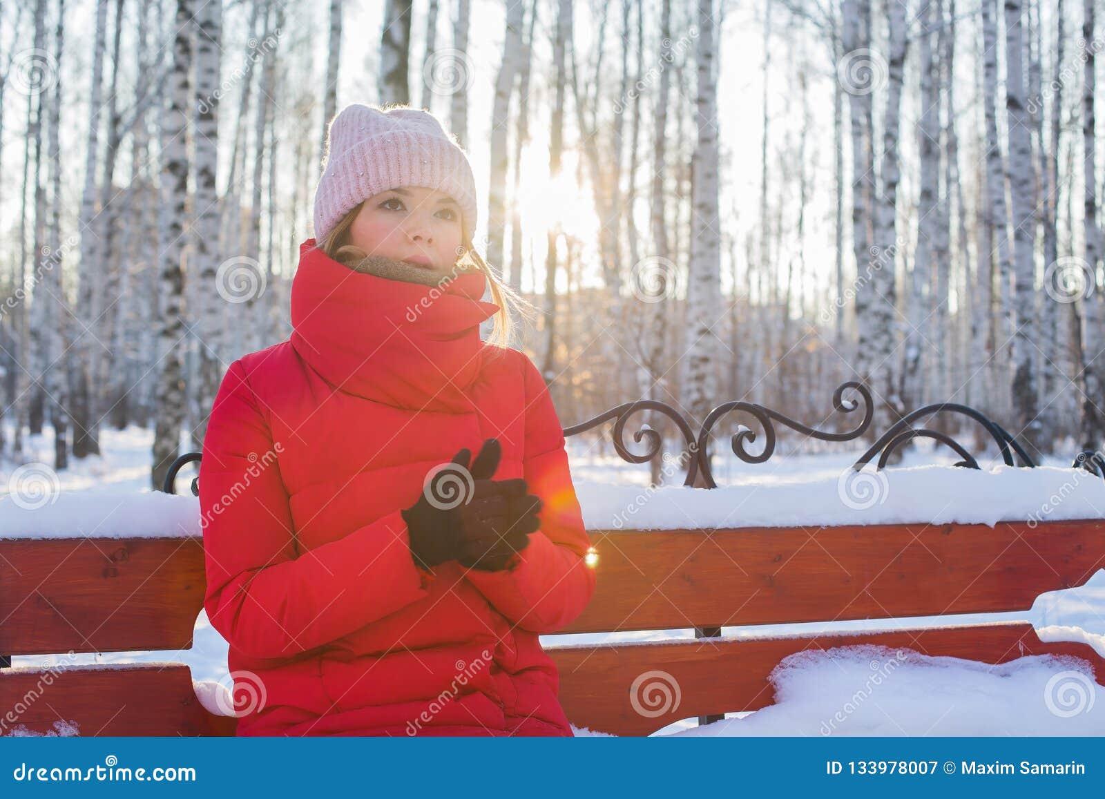 La jeune belle femme dans la veste chaude rouge s assied sur le banc en parc imagé avec des bouleaux et chauffe des mains dans le