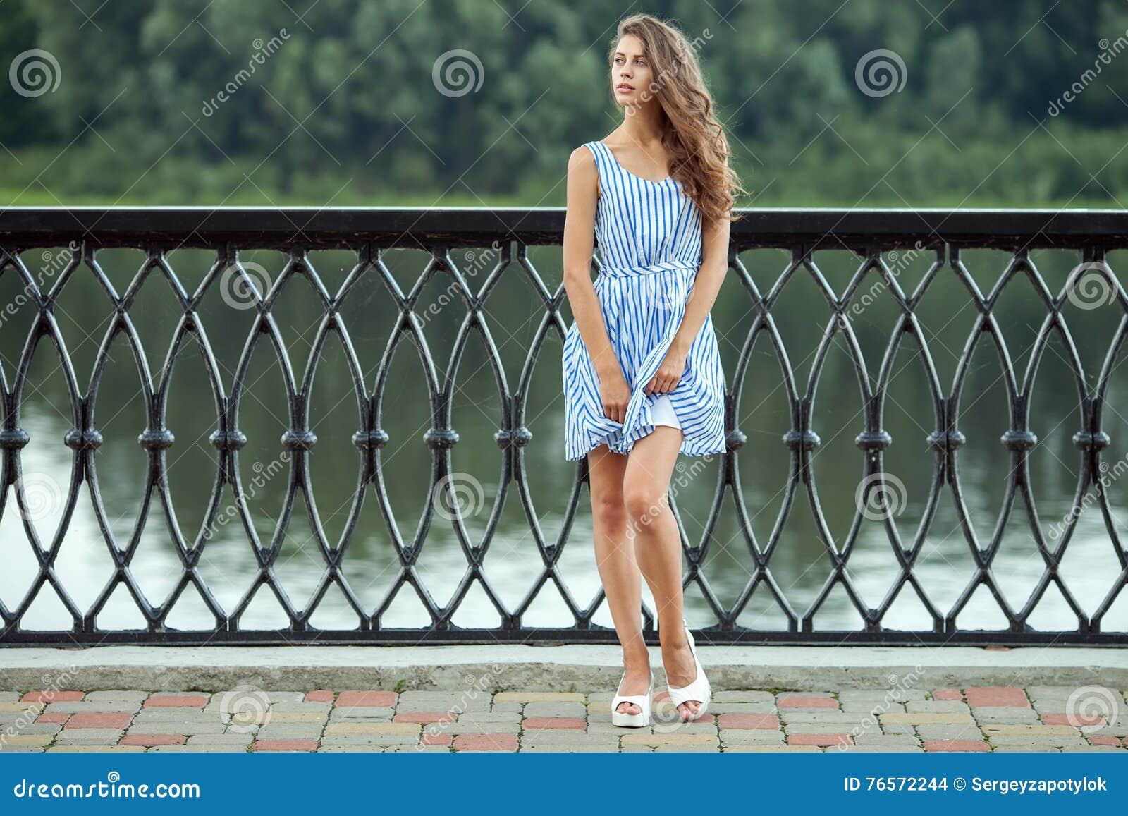 La jeune belle femme de portrait intégral dans le bleu blanc a barré la robe, parc de rver d été dehors