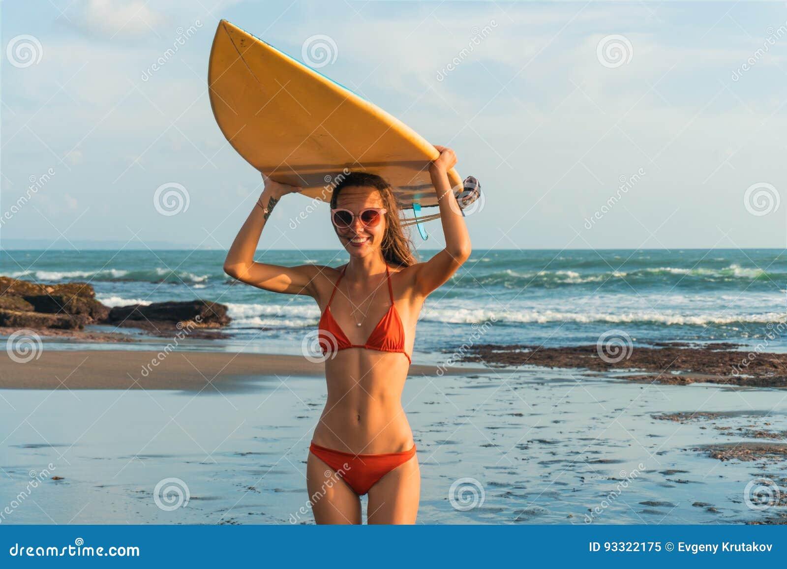 La jeune belle femme en verres rouges de bikini et de soleil tient dans des mains un ressac sur la plage d océan au coucher du so