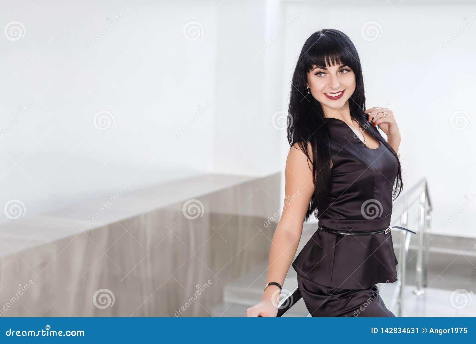 La jeune belle femme heureuse de brune habillée dans un costume noir avec une jupe courte se tient contre le mur blanc dedans