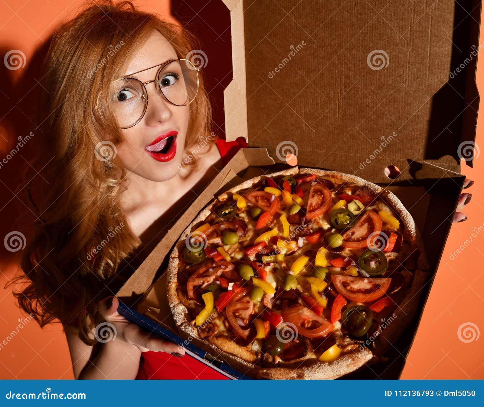 La jeune belle femme mangent de la pizza entière végétarienne mexicaine dans la boîte sur l orange