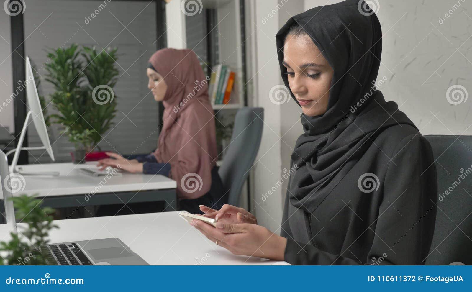 La jeune belle fille dans le hijab noir sassied dans le bureau et