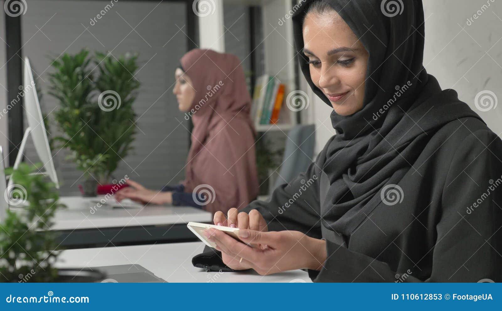 La jeune belle fille dans le hijab noir s assied dans le bureau et