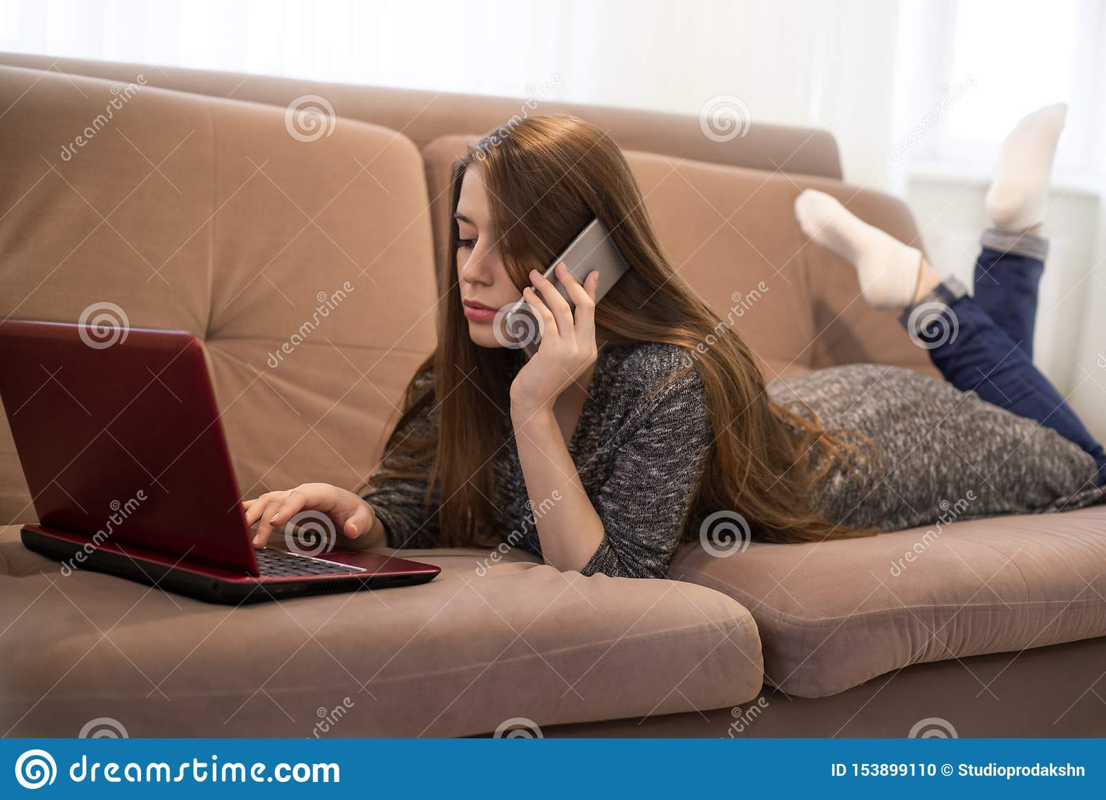 La jeune belle fille de brune se trouvant sur le sofa avec ses jambes a croisé parler sur le téléphone et le film de observation