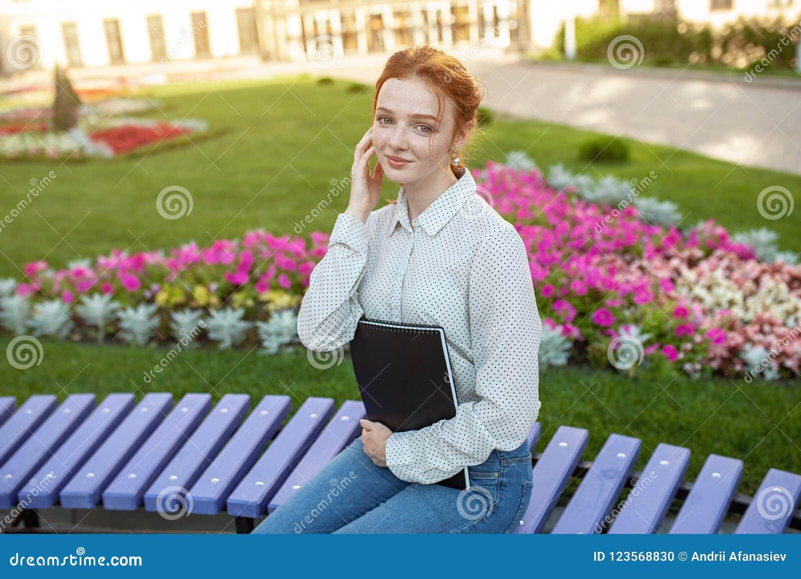 La jeune belle fille rousse avec des taches de rousseur se reposant sur un banc près de l université tient un carnet dans des ses