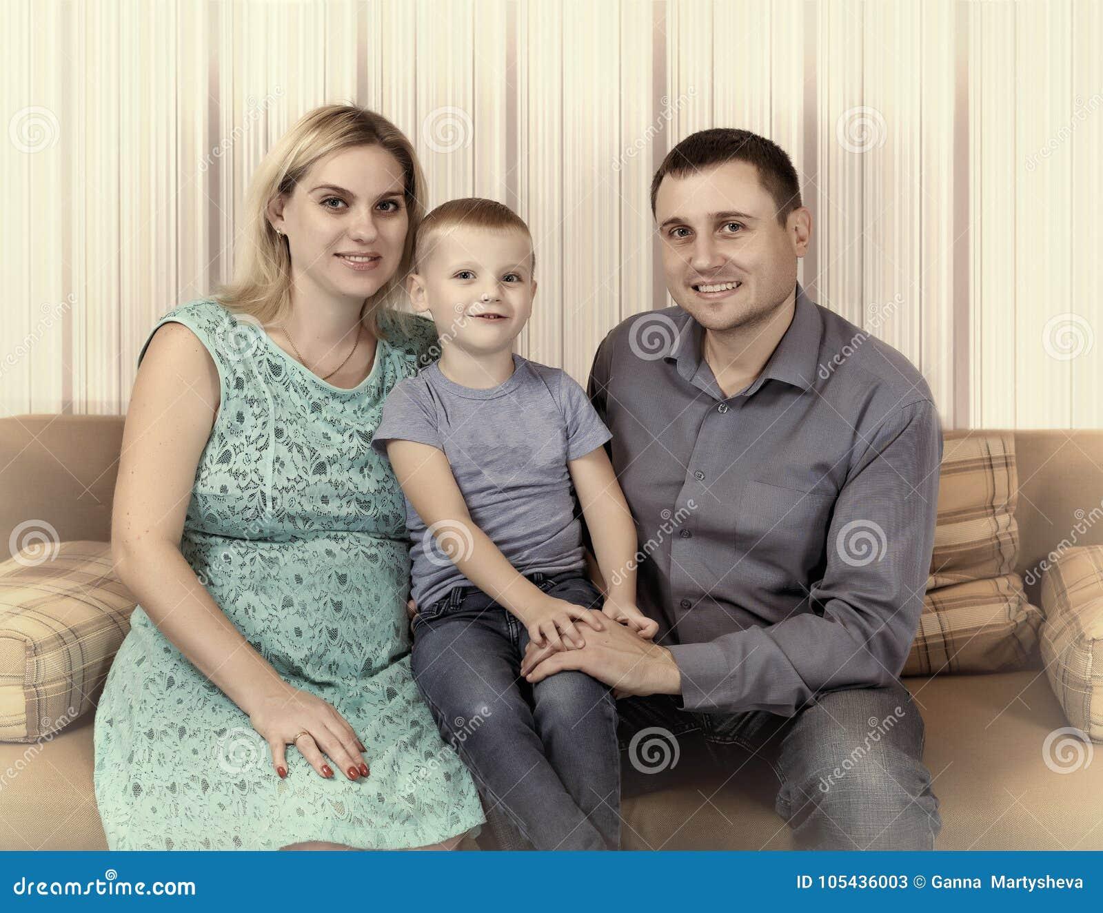La jeune famille se repose à la maison sur le divan Une mère enceinte, un petit fils et un père