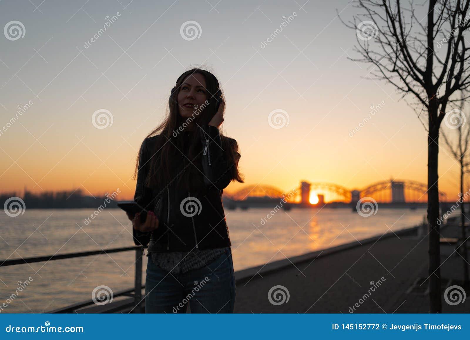 La jeune femme écoute la musique dans des écouteurs fermés par son téléphone presque utilisant une veste en cuir et des jean