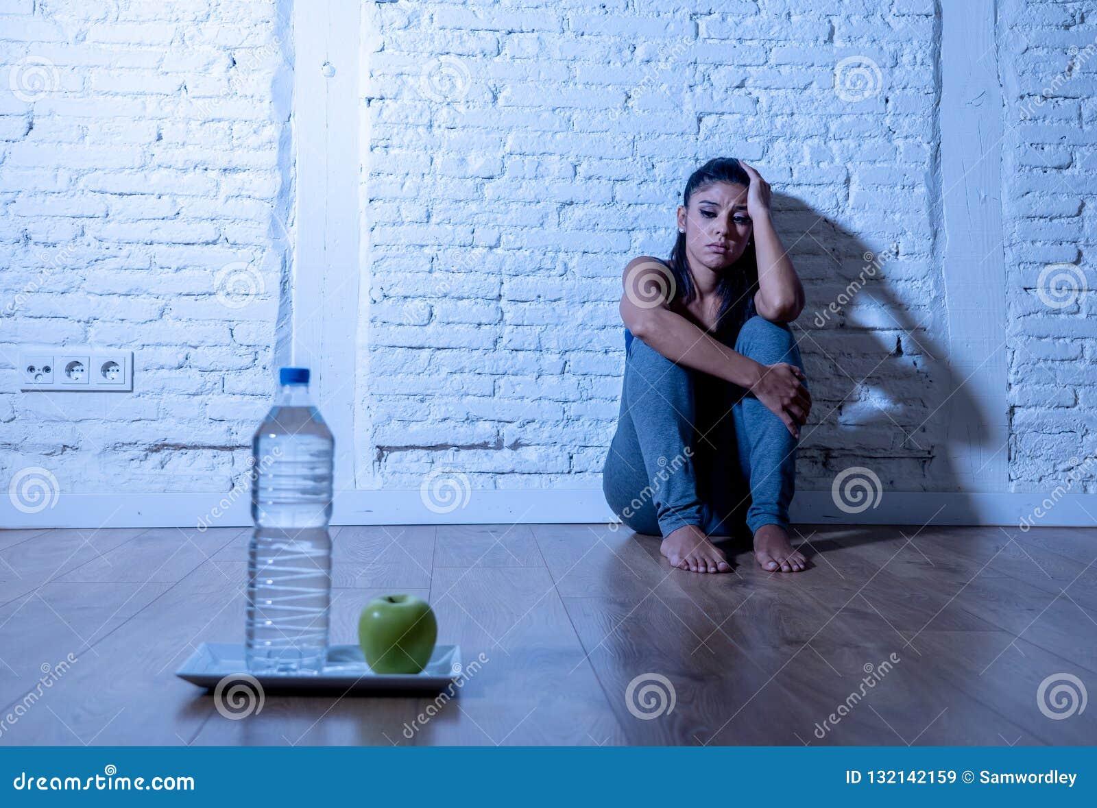 La jeune femme affamée déprimée sur la pomme et l eau suivent un régime