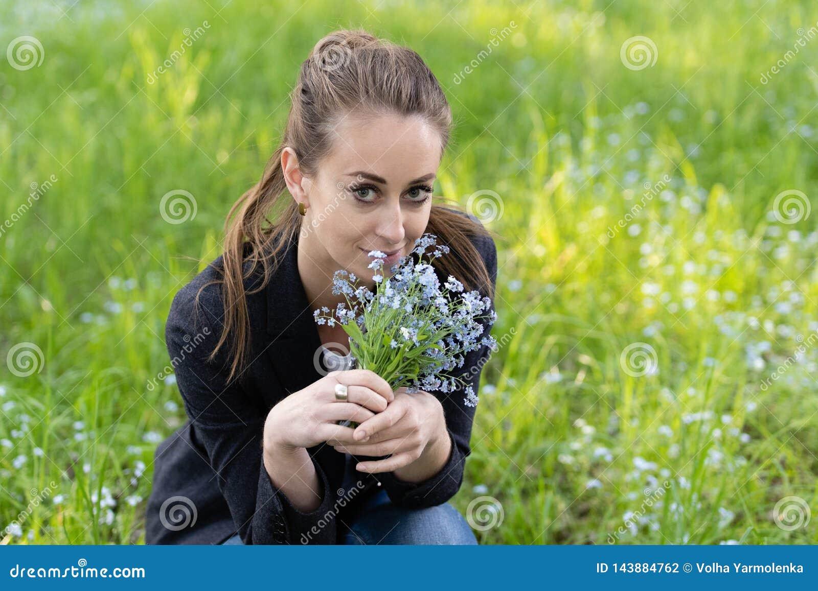 La jeune femme attirante a apporté un bouquet des myosotis des marais à son visage