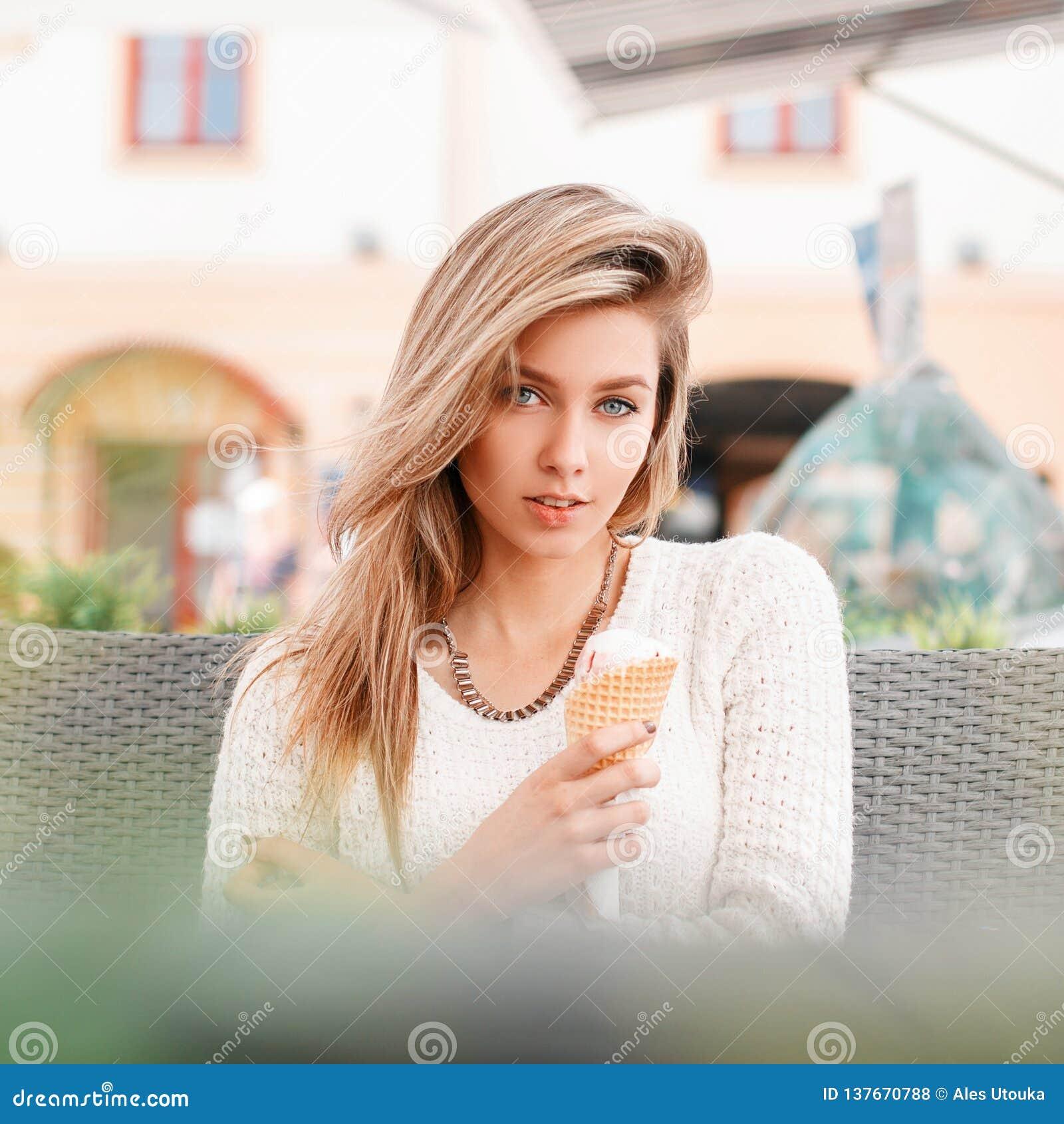 La jeune femme attirante dans un chandail tricoté blanc à la mode avec la crème glacée douce s assied dedans dans un café extérie
