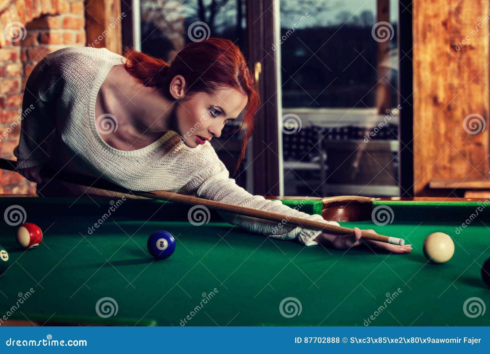 La jeune femme attirante joue le jeu de la table de billard de billard Amusement et concept de concurrence