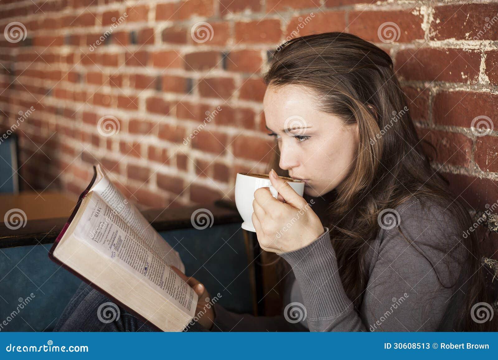 La jeune femme avec la tasse de café blanc lit sa bible
