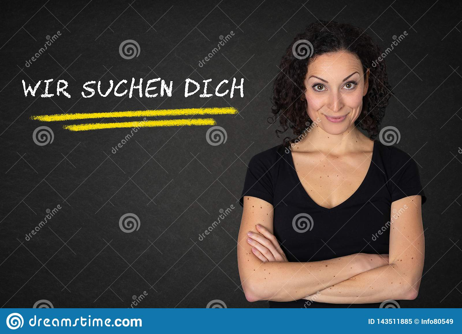 """La jeune femme avec les bras croisés et le """"Wir texte suchen dich """"sur un fond de tableau noir Traduction : """"Nous vous rec"""