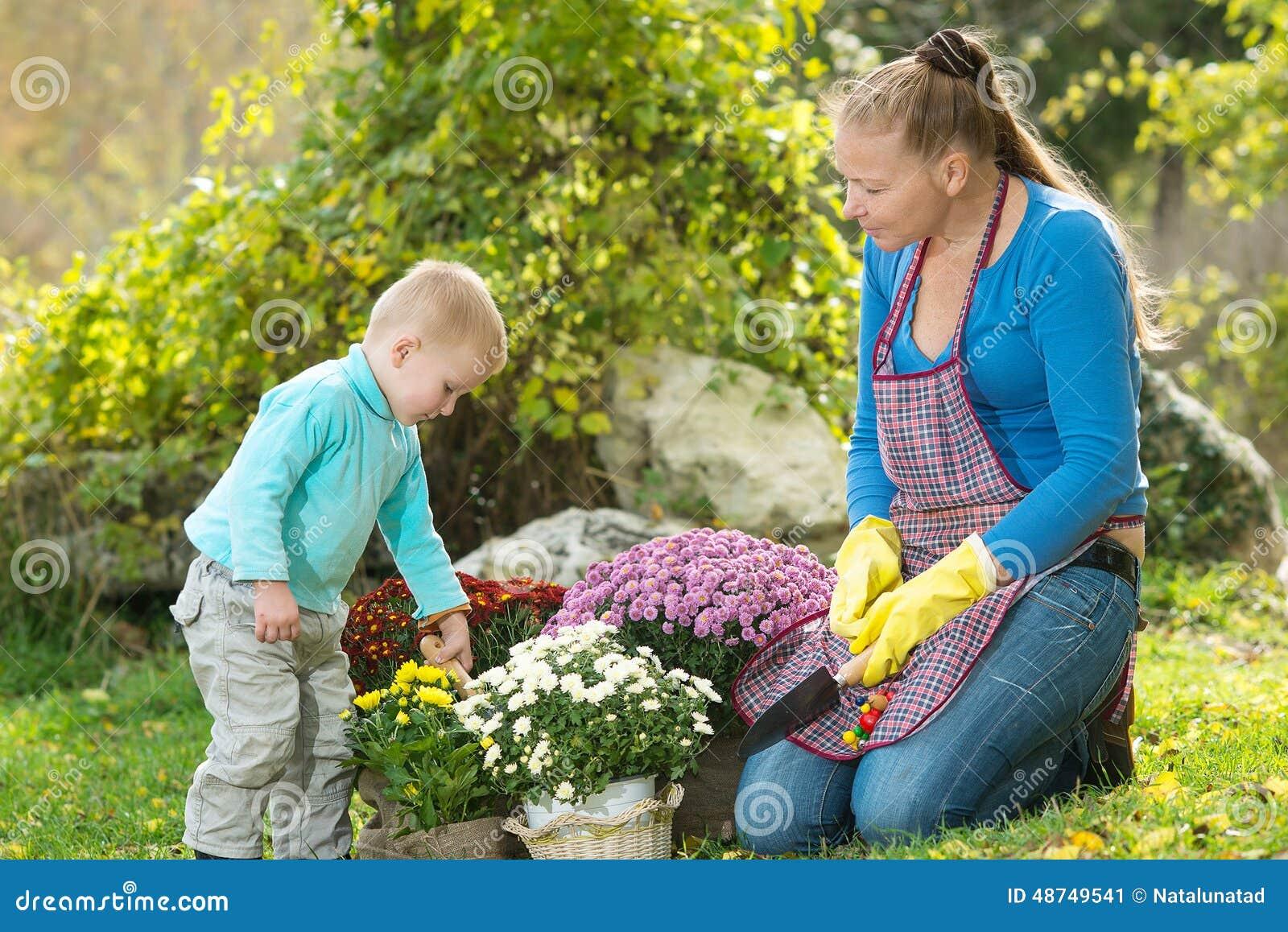 La jeune femme avec un enfant plantent des fleurs