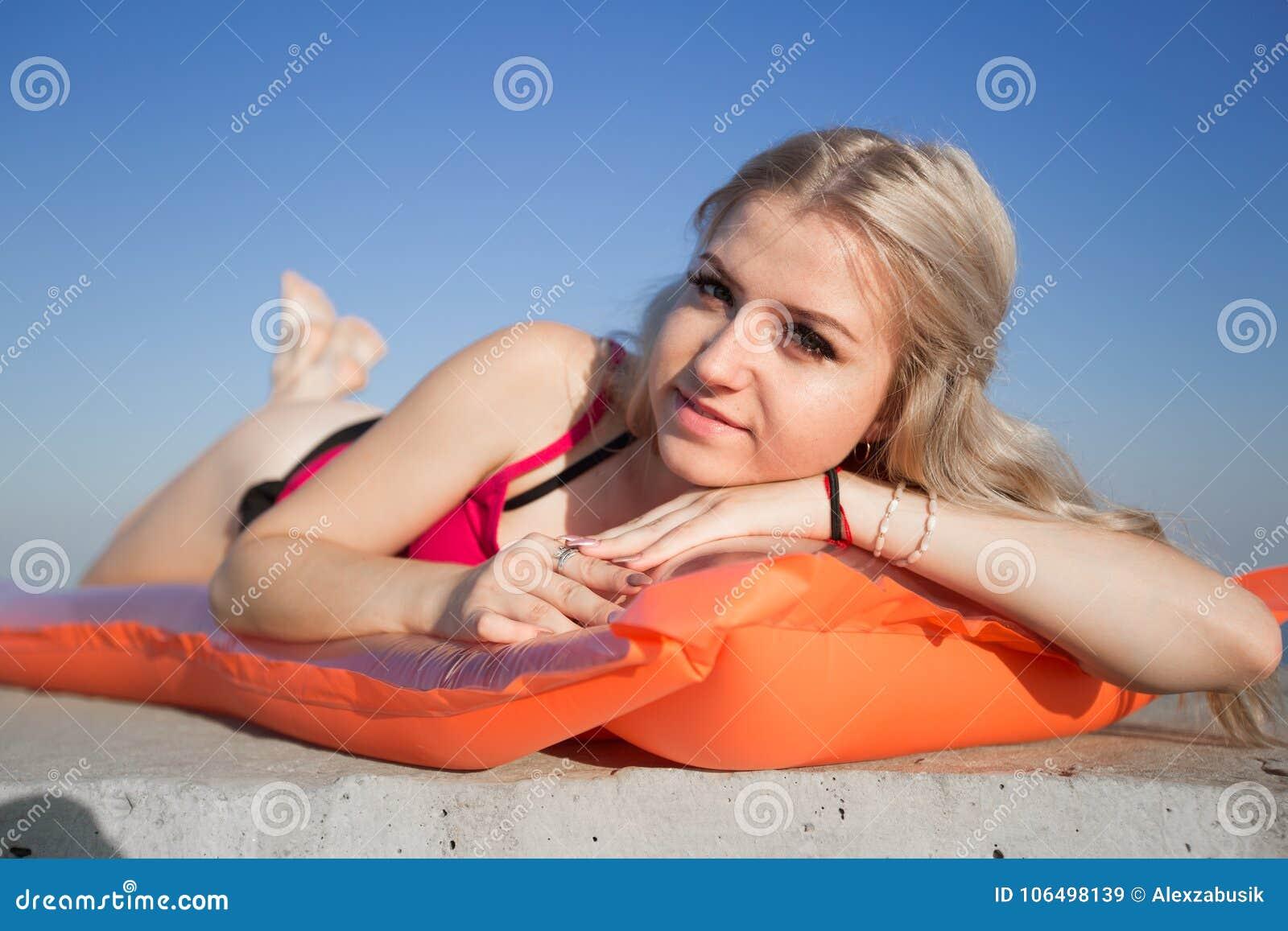 La jeune femme blonde la prend un bain de soleil sur le radeau de piscine regardant l appareil-photo