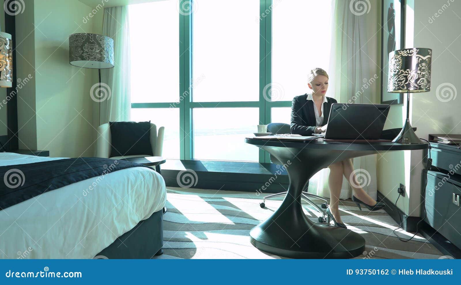 La jeune femme blonde sexy d affaires travaille dans la chambre d