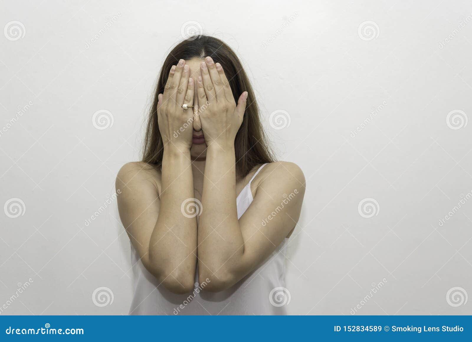 La jeune femme caucasienne cache ses yeux avec ses paumes