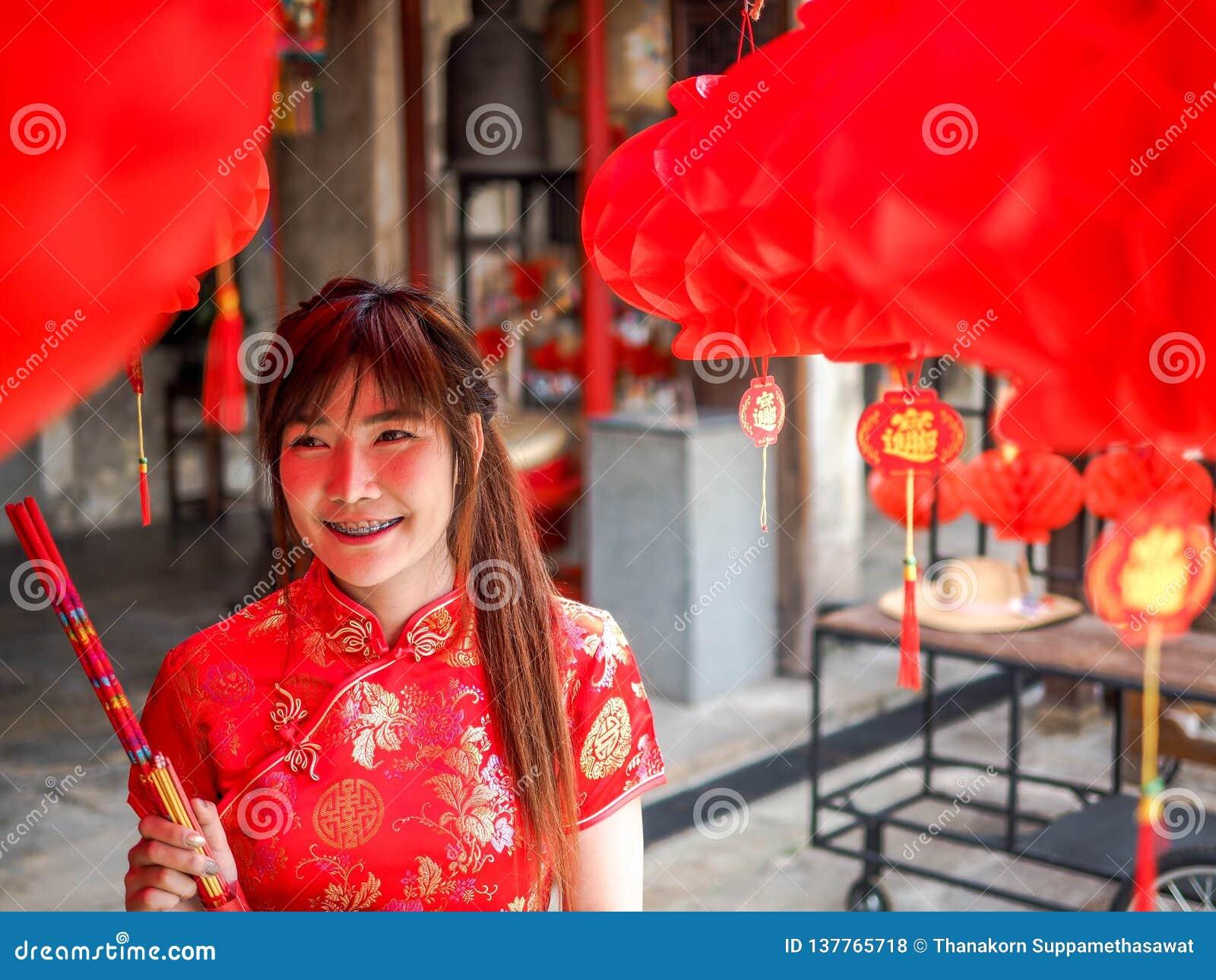 La jeune femme chinoise avec l habillement de tradition tenant des bâtons d encens exaspèrent, nouvelle année chinoise