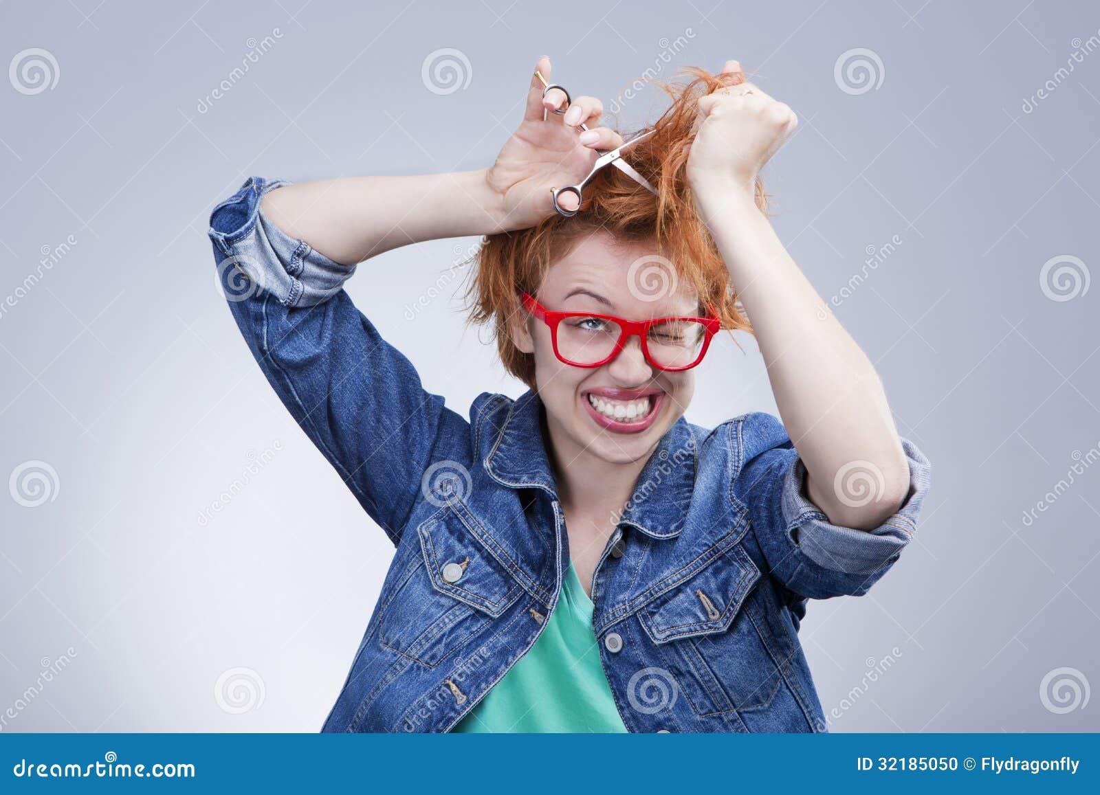 La jeune femme coupe ses cheveux avec la coiffure de ciseaux
