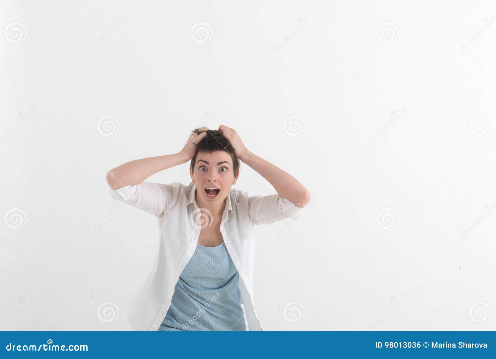 La jeune femme criant dans la terreur avec des mains sur sa tête, disent regarder du bout des lèvres grand ouvert dans la panique