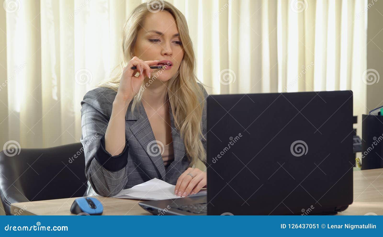 La jeune femme d affaires dans le costume travaille à l ordinateur dans le bureau