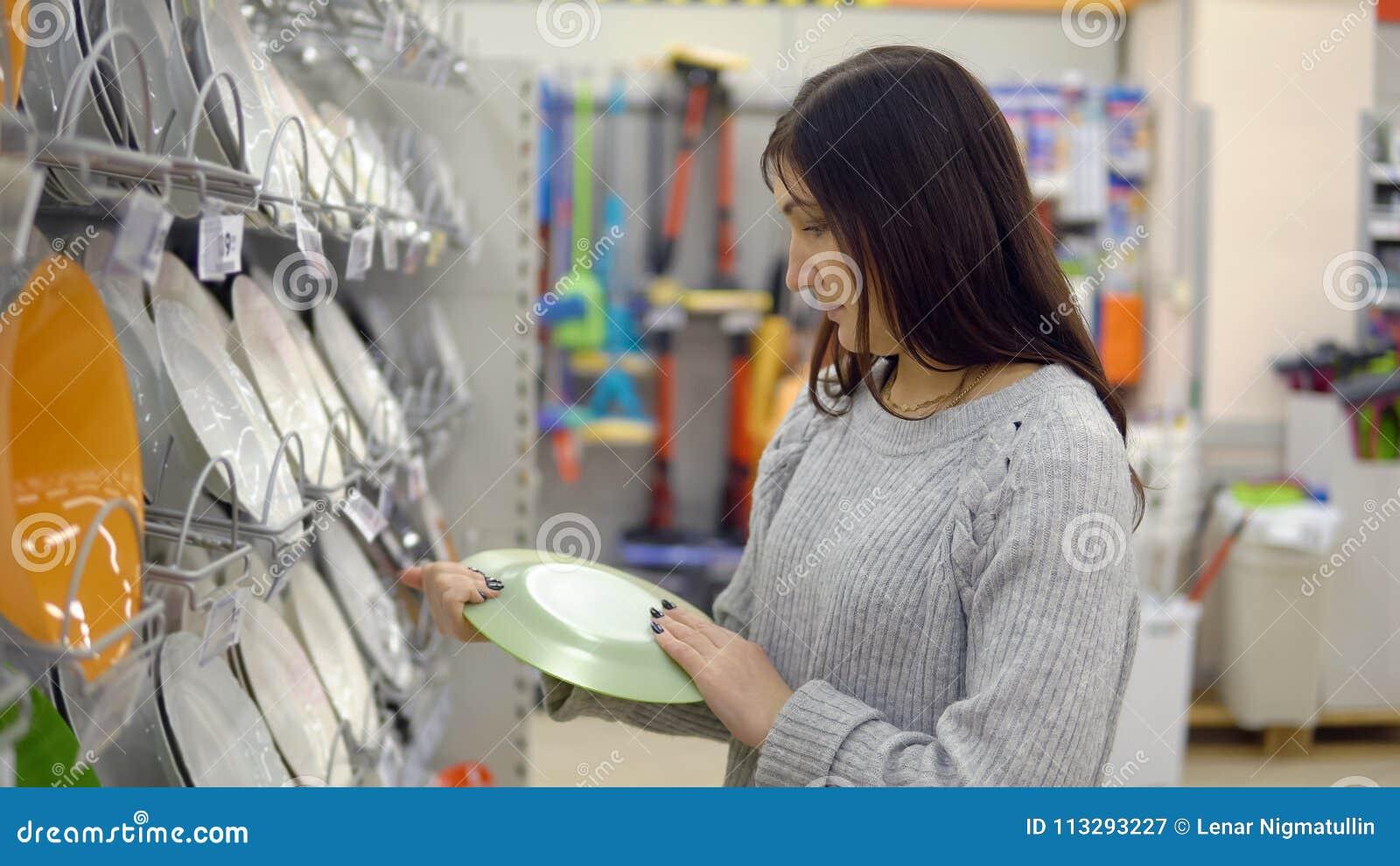 La jeune femme dans un magasin de biens d équipement ménager choisit des plats