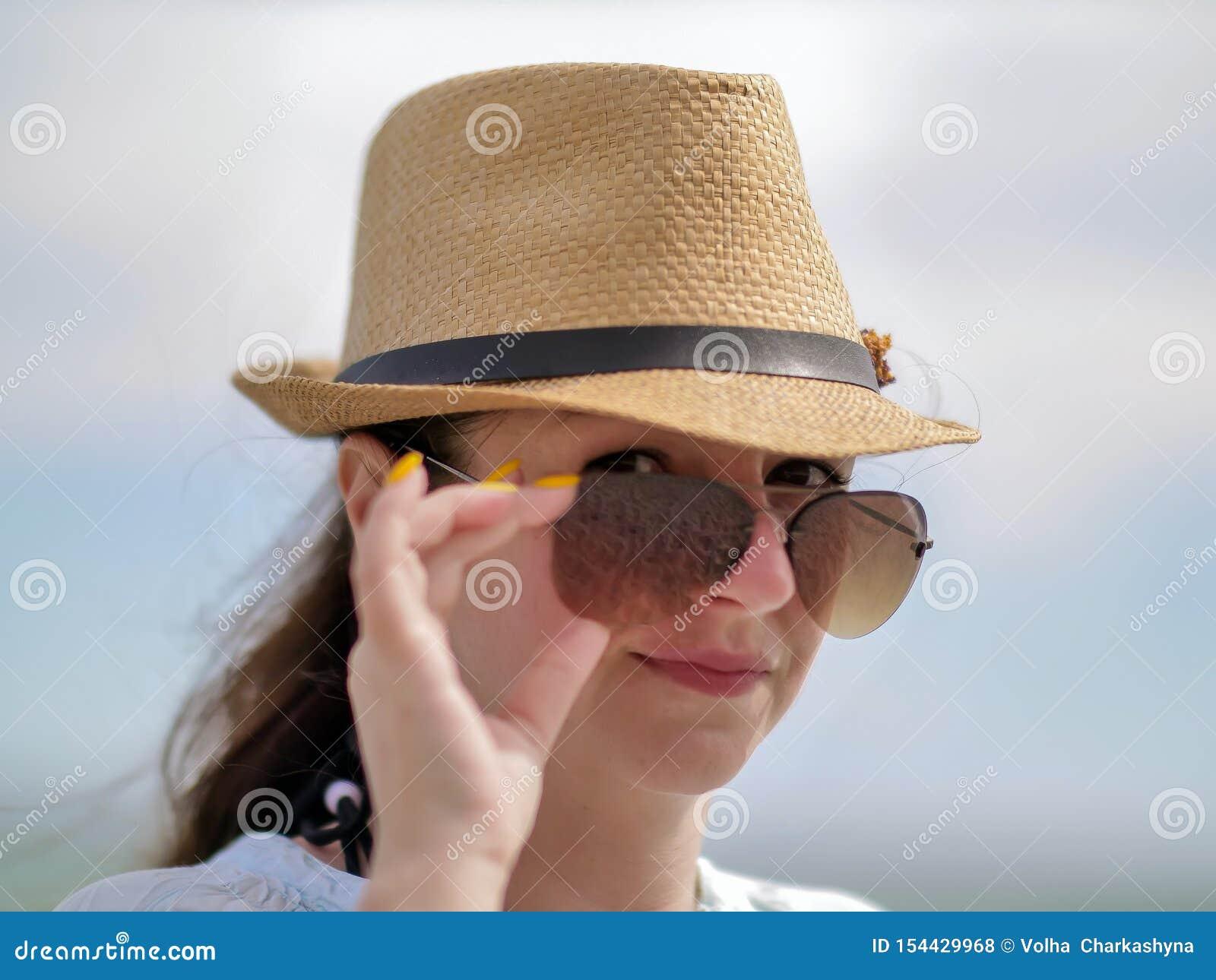 La jeune femme de brune redresse des lunettes de soleil sur son visage, regard sexy, regarde dans la caméra