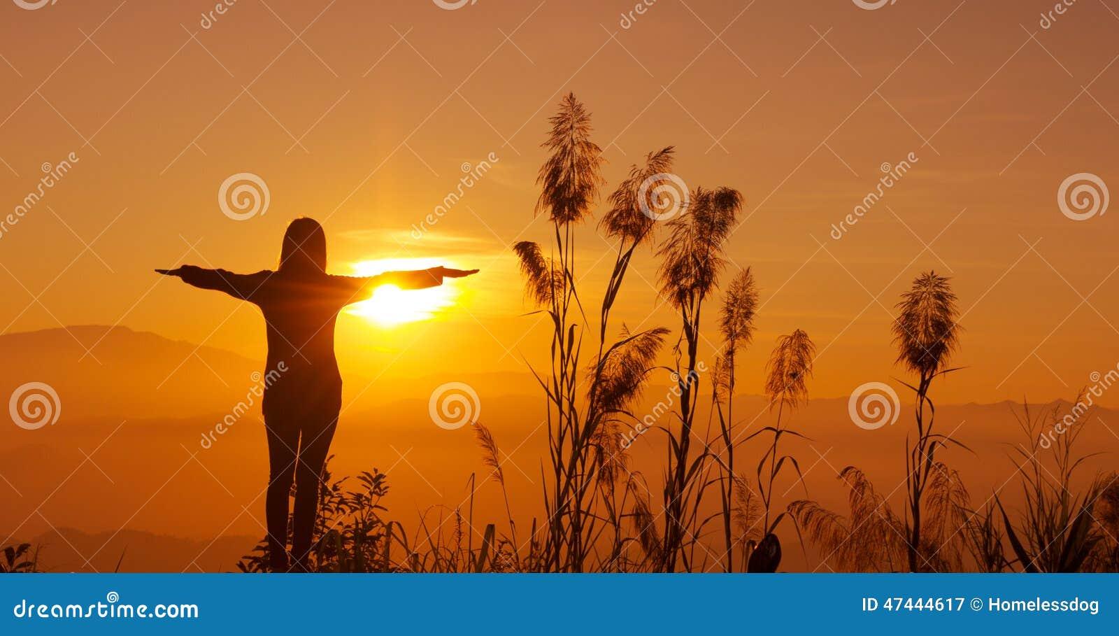La jeune femme de silhouette de coucher du soleil se sentant à la liberté et détendent