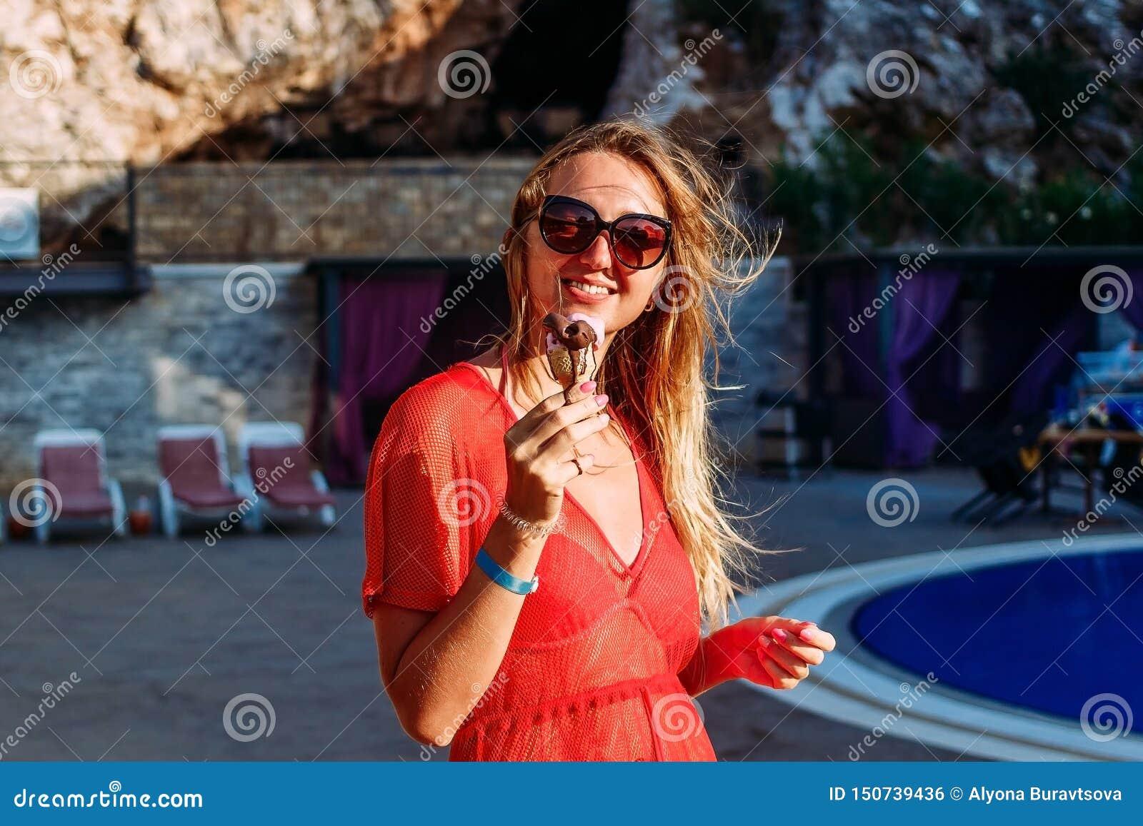 La jeune femme de sourire mange la crème glacée de chocolat en été