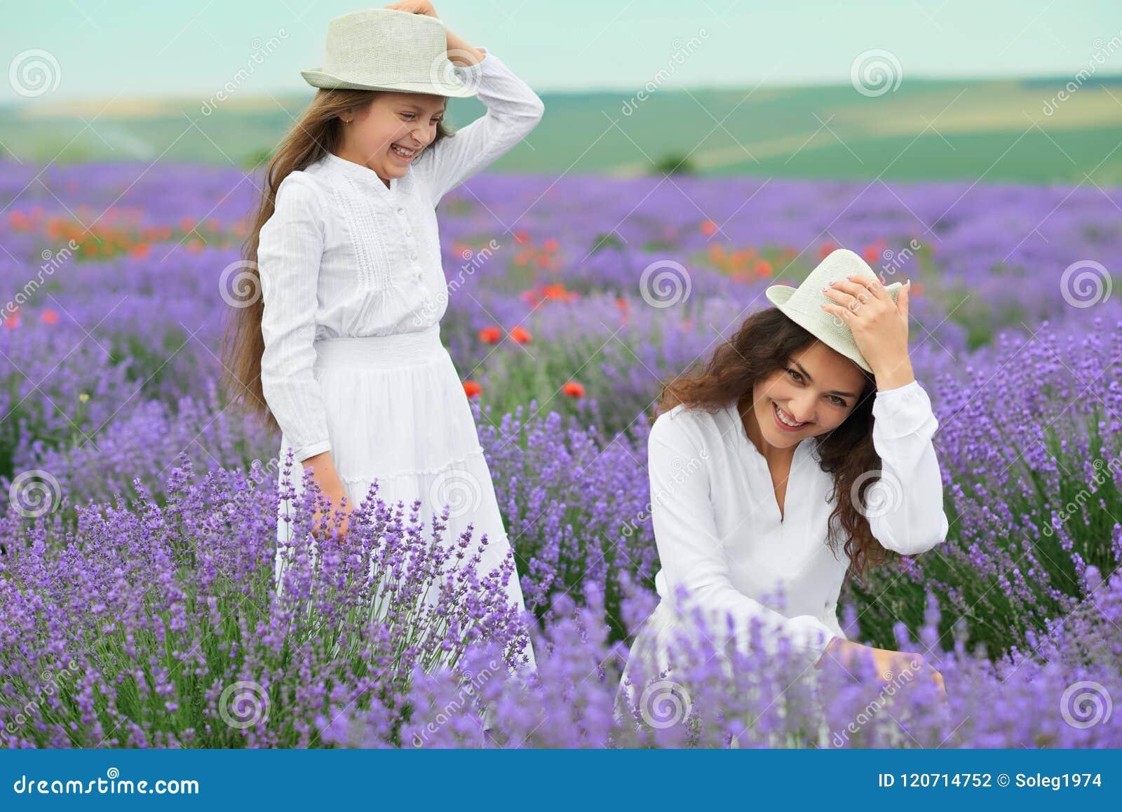 La jeune femme et la fille sont dans le domaine de lavande, beau paysage d été avec les fleurs rouges de pavot