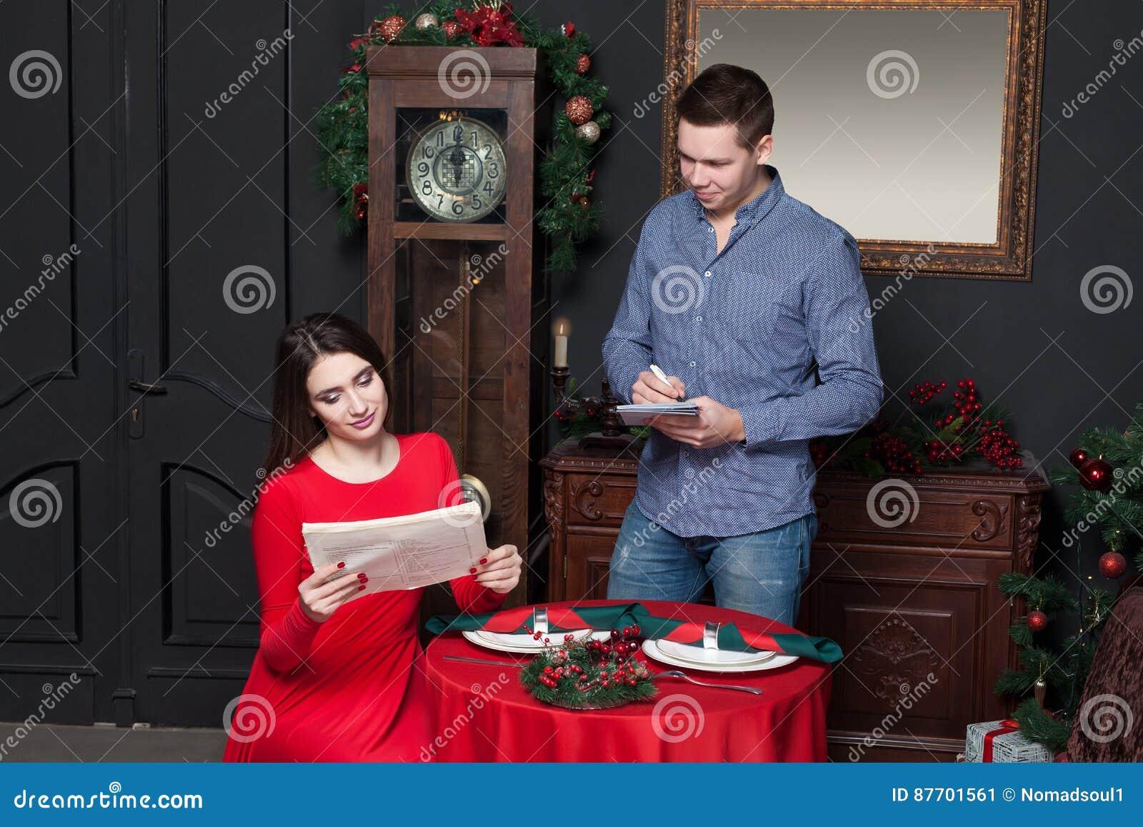 La jeune femme explorent le menu au restaurant de luxe