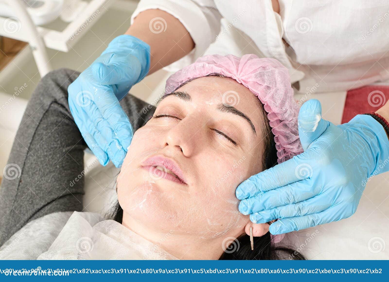 La jeune femme fait le massage facial professionnel dans le salon de beaut?