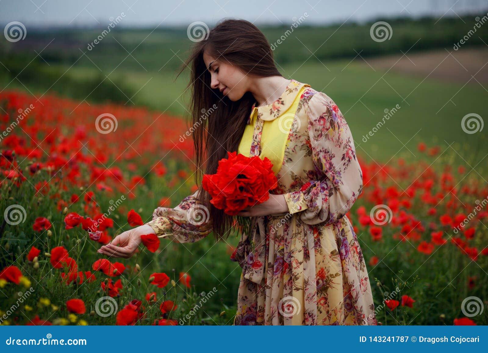 La jeune femme gaie avec aux cheveux longs, contact adoucissent une fleur de pavots, posant dans un domaine de fleurs, fond de fl