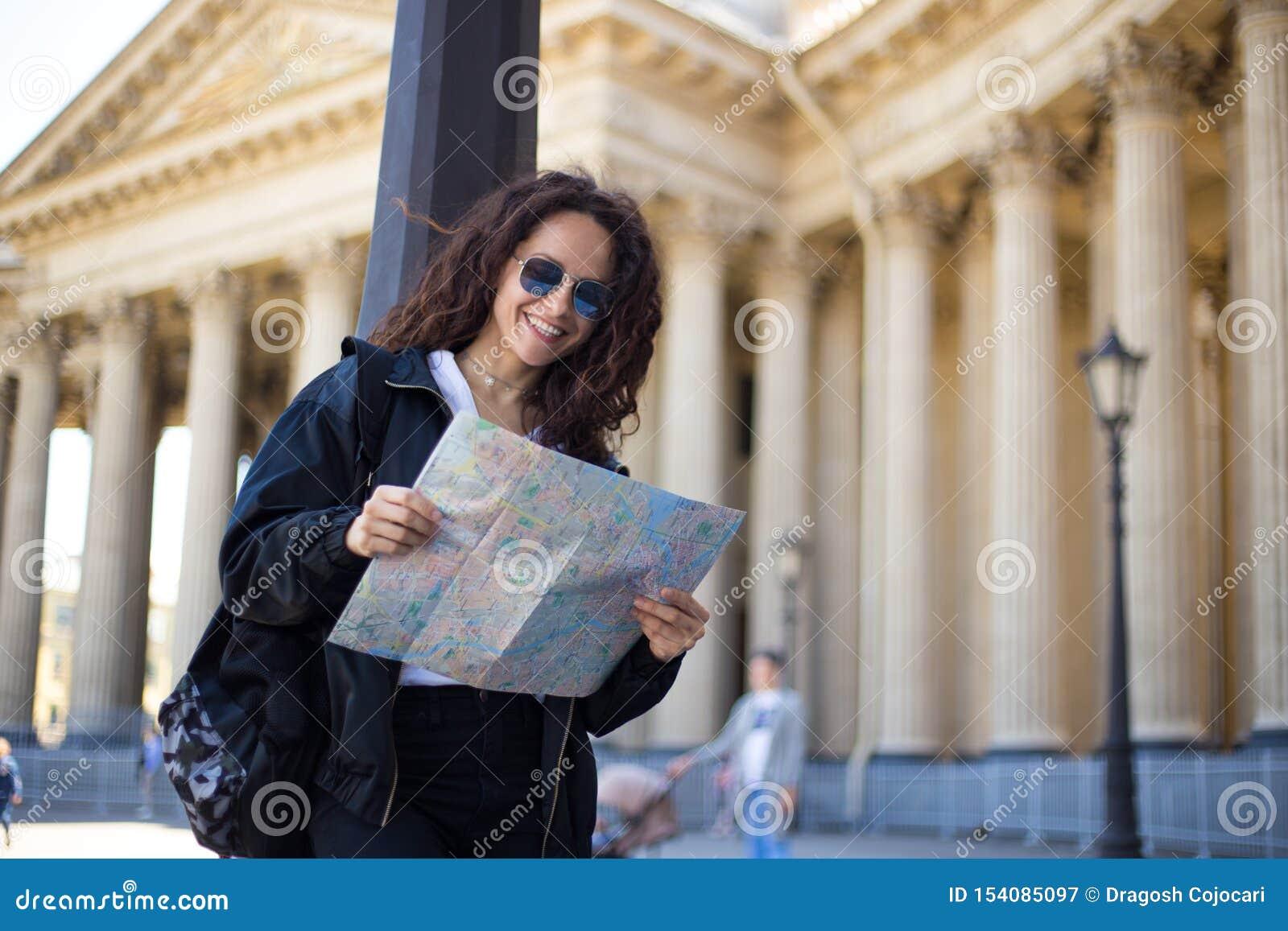 La jeune femme gaie dans le noir, dans des lunettes de soleil avec une carte de papier de ville dans des mains, ont un sac à dos,