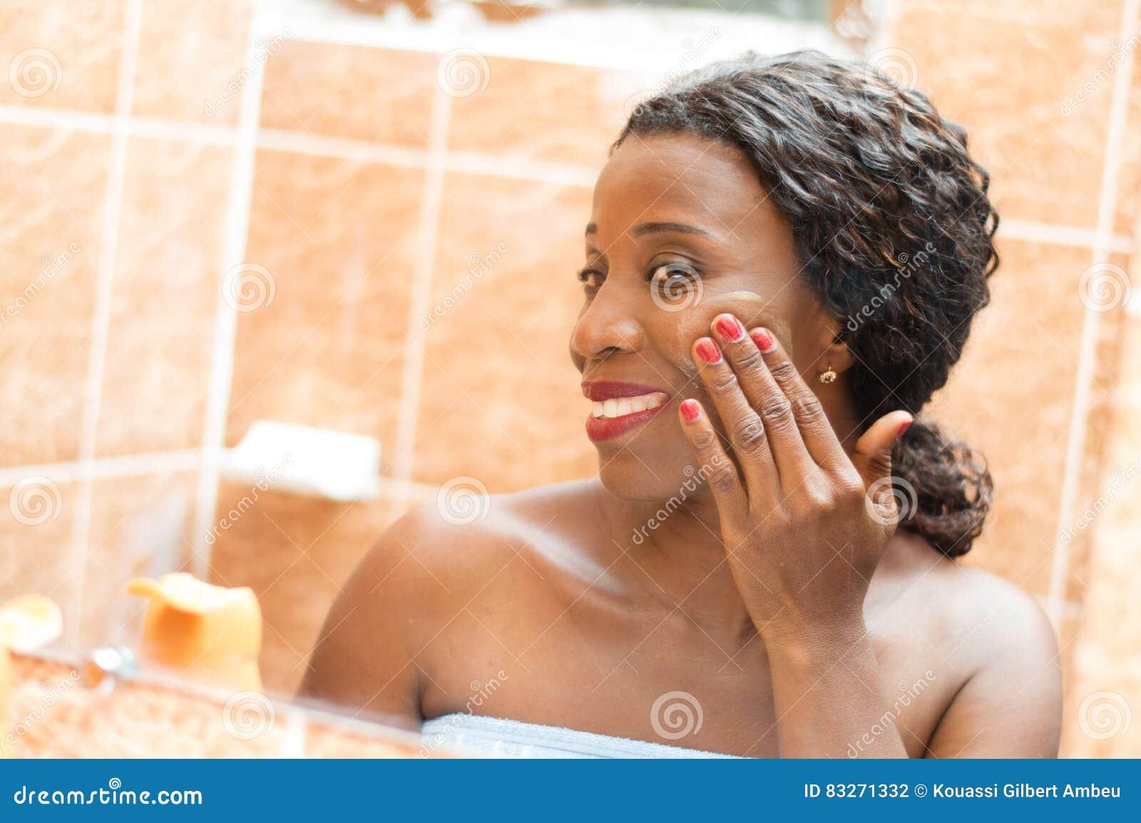 La jeune femme heureuse applique la crème sur son visage