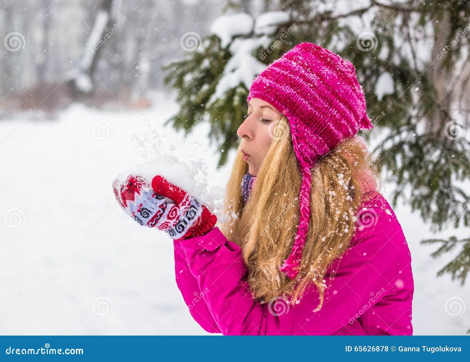 La jeune femme heureuse apprécient la neige en parc de ville d hiver extérieur