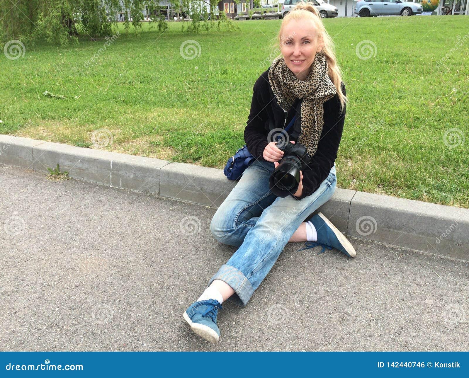 La jeune femme heureuse avec une grande caméra de miroir s assied sur la pelouse par la route