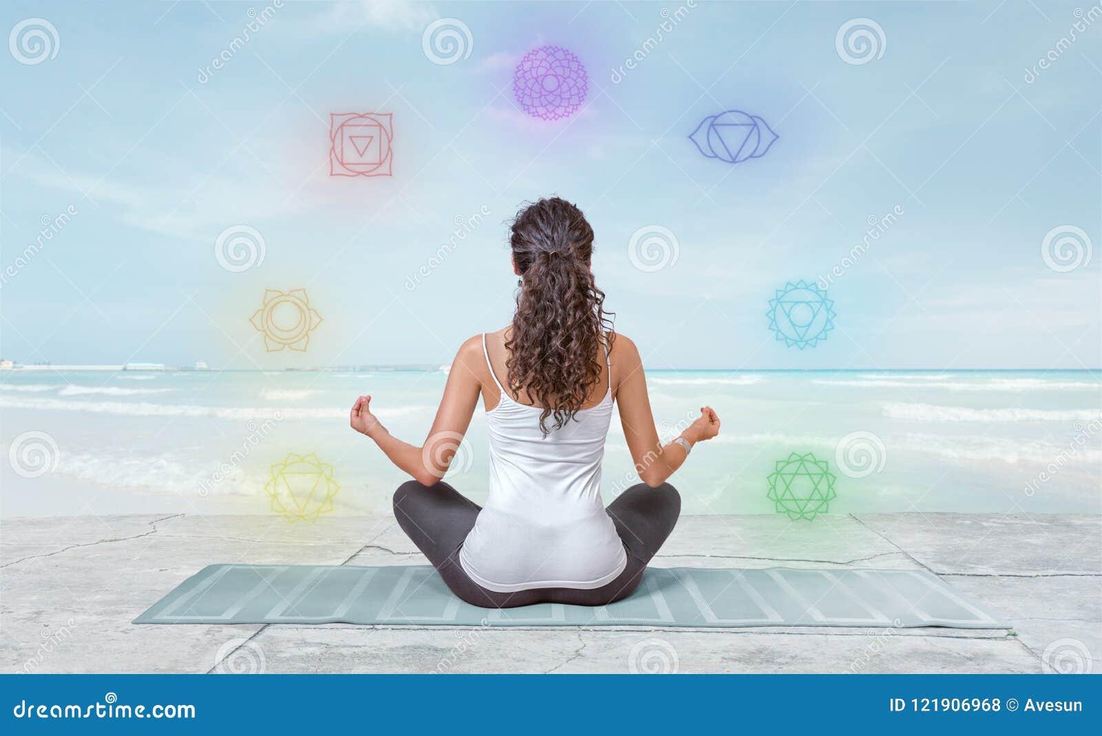 La jeune femme médite sur la plage avec des chakras rougeoyant autour de elle