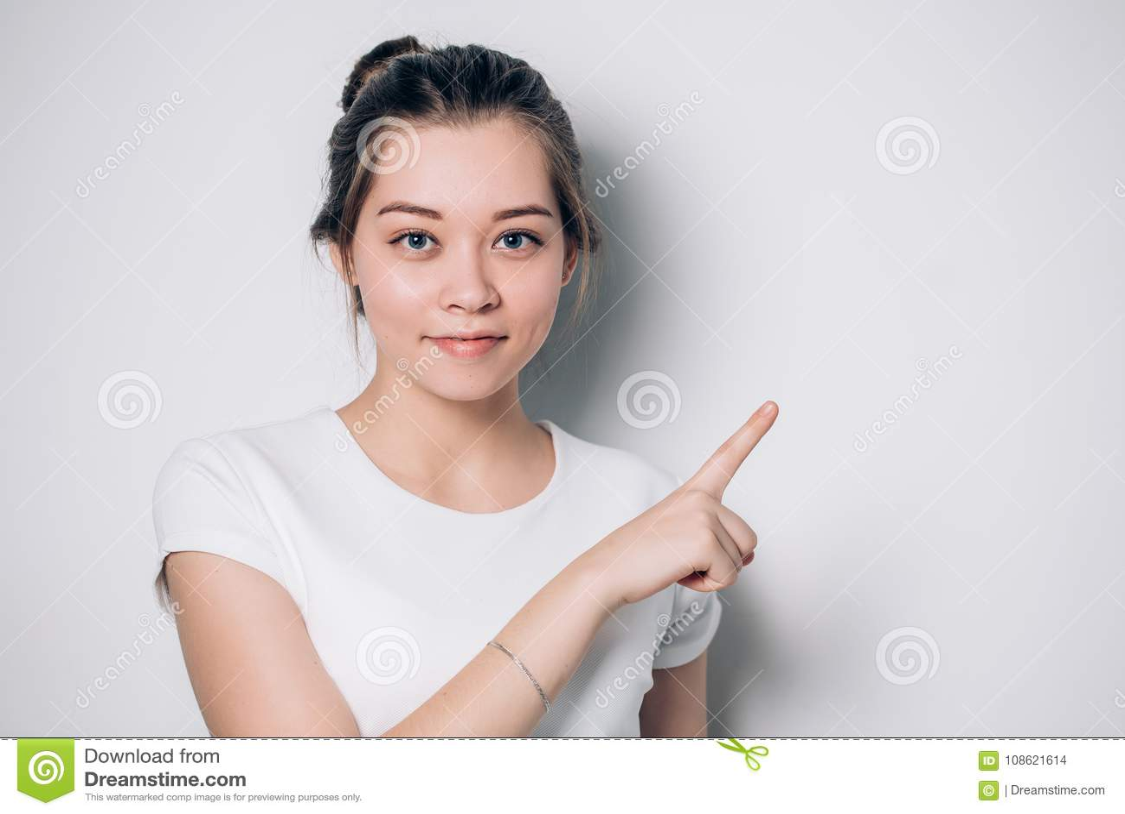 La jeune femme mignonne dirige un doigt loin Présentation de votre produit