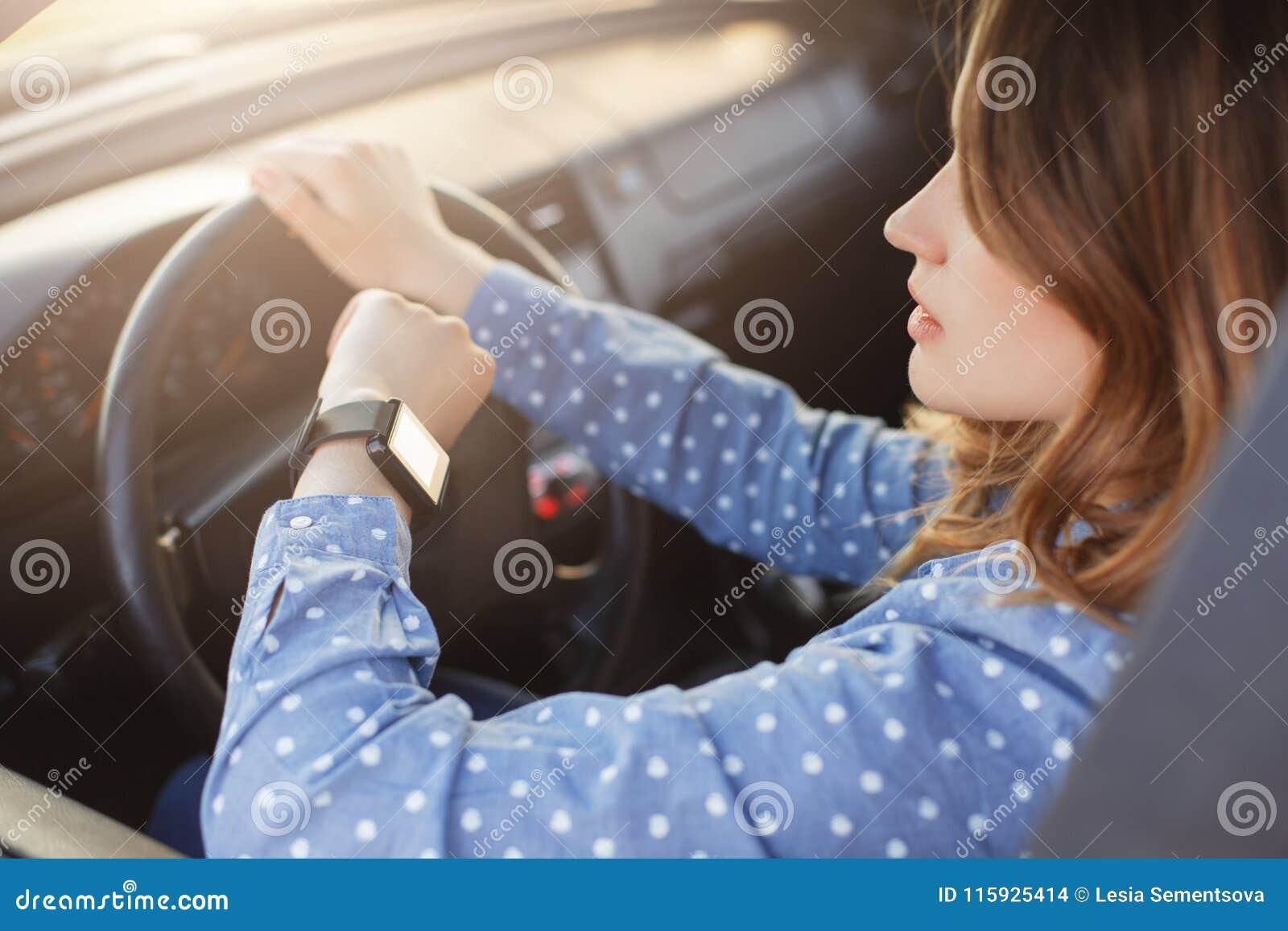 La jeune femme occupée conduit la voiture et regarde la montre, coincée dans l embouteillage, des hâtes au travail, étant nerveus