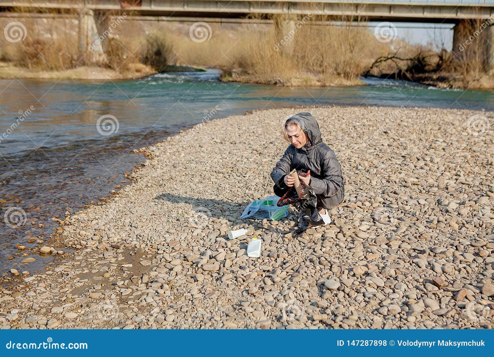 La jeune femme rassemblant les d?chets en plastique de la plage et les mettant dans les sachets en plastique noirs pour r?utilise