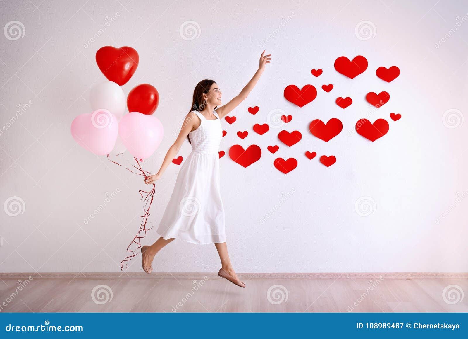 La jeune femme romantique avec des ballons s approchent du mur