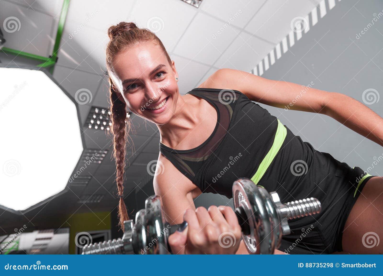 La jeune femme sûre faisant le biceps courbent l exercice avec des haltères  au centre de 9e0494c54b1
