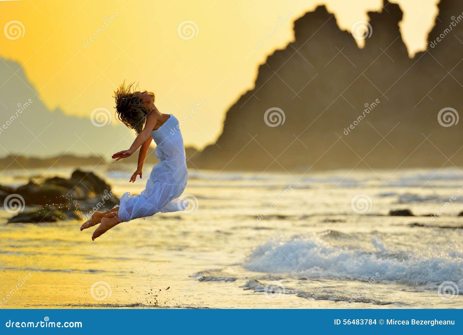 La jeune femme sautant sur la plage en été