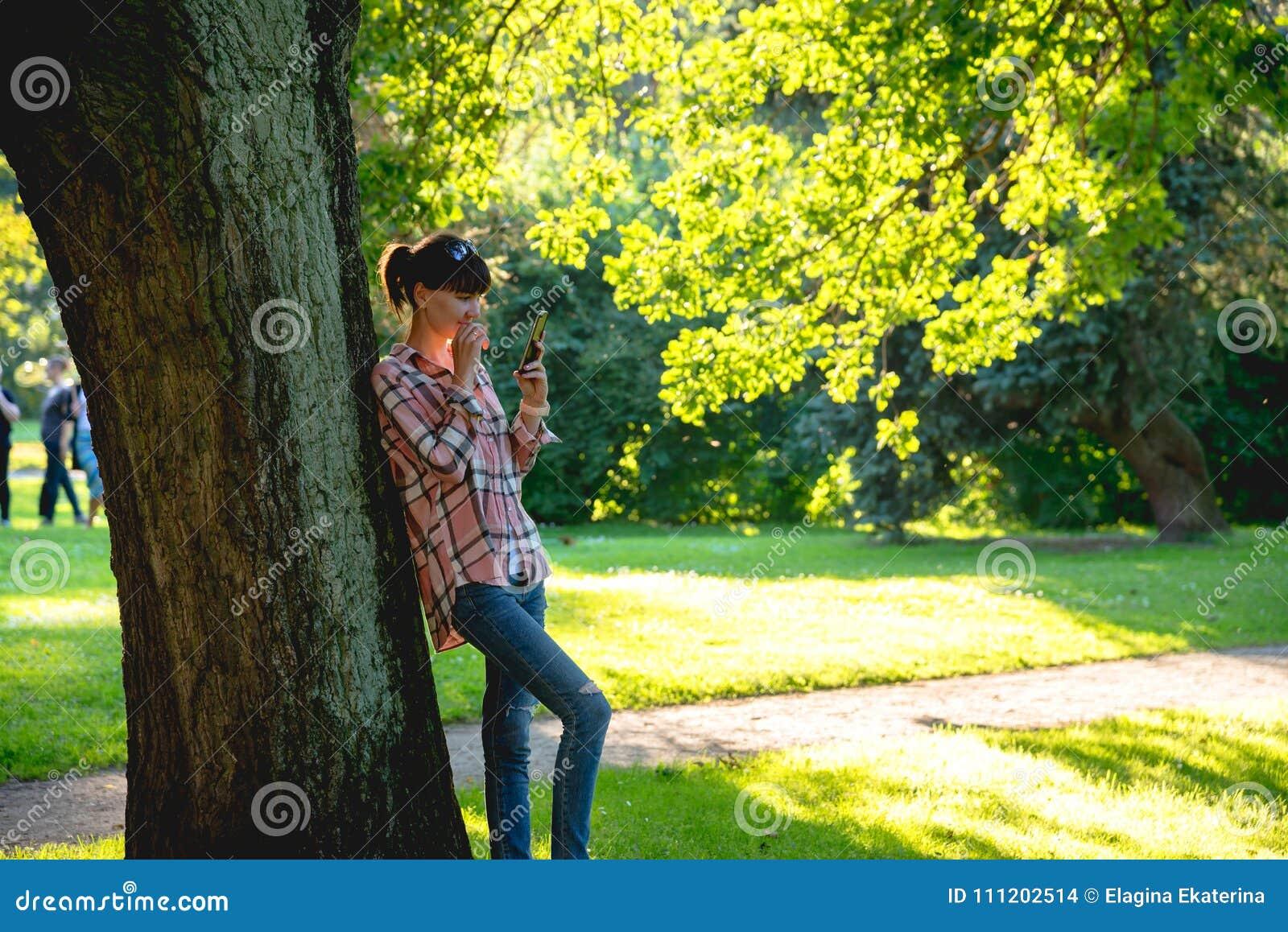La jeune femme se tient sous un arbre avec un téléphone dans des mains en Th