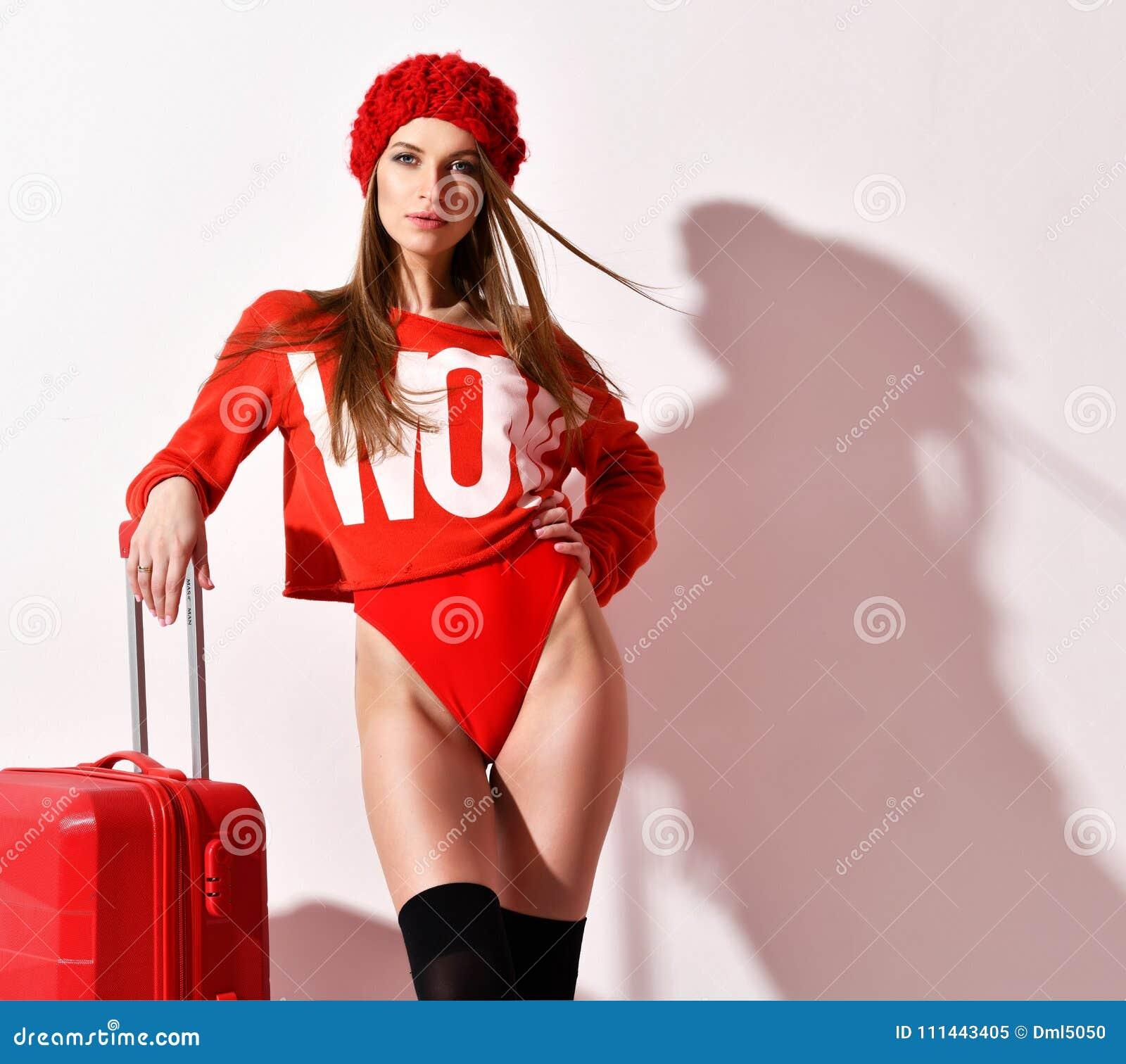 La jeune femme sexy en tissu rouge de corps de mode et le chapeau avec le bagage de voyageur mettent en sac sur le blanc