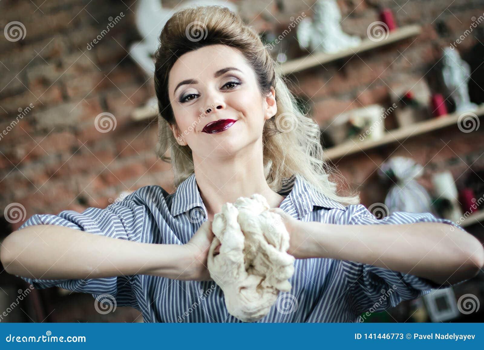 La jeune femme sexy prépare la pâte dans la cuisine La fille blonde sur la cuisine malaxe la pâte à la main Jeune femme heureuse