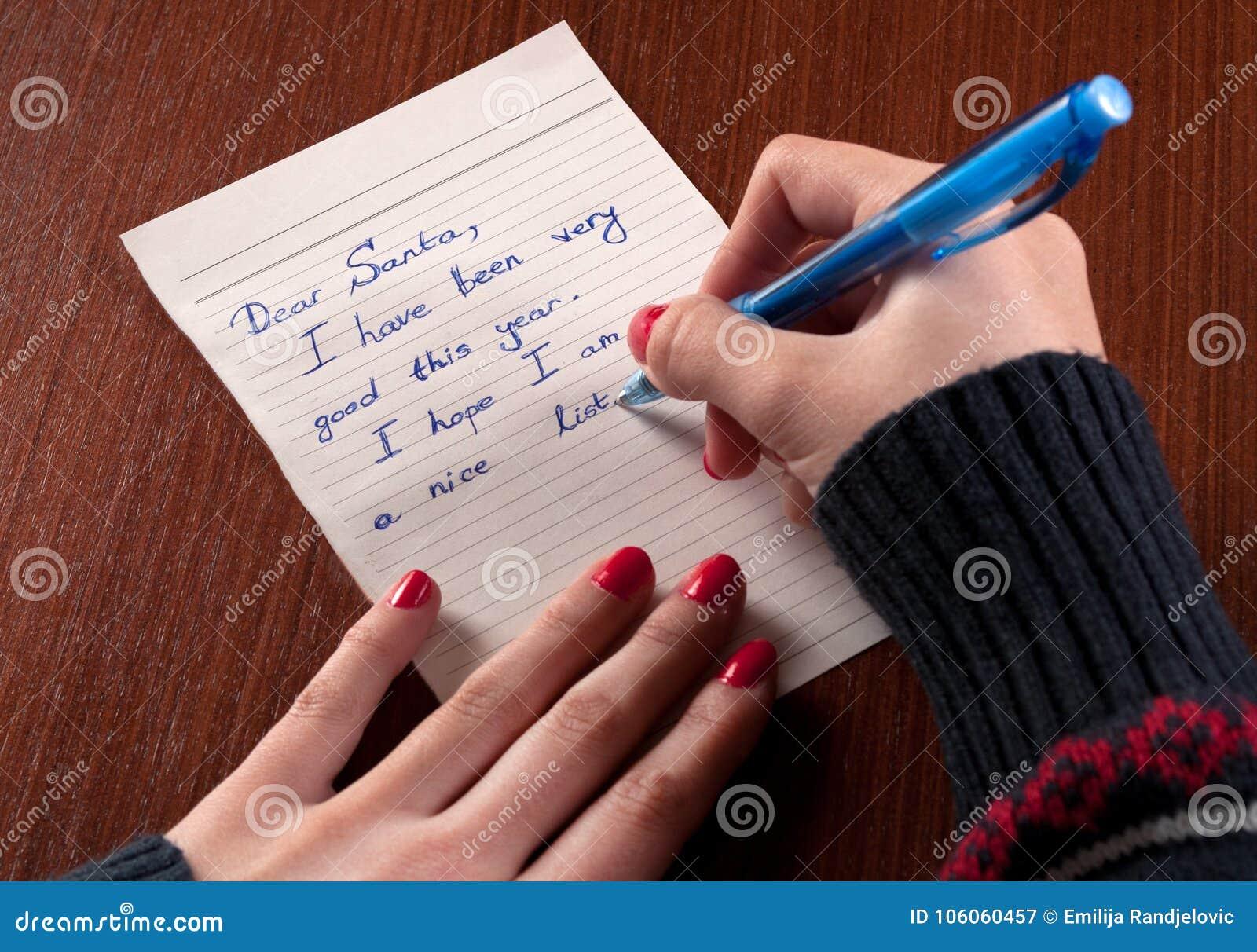La jeune fille écrit la lettre à santa claus sur le bureau et le