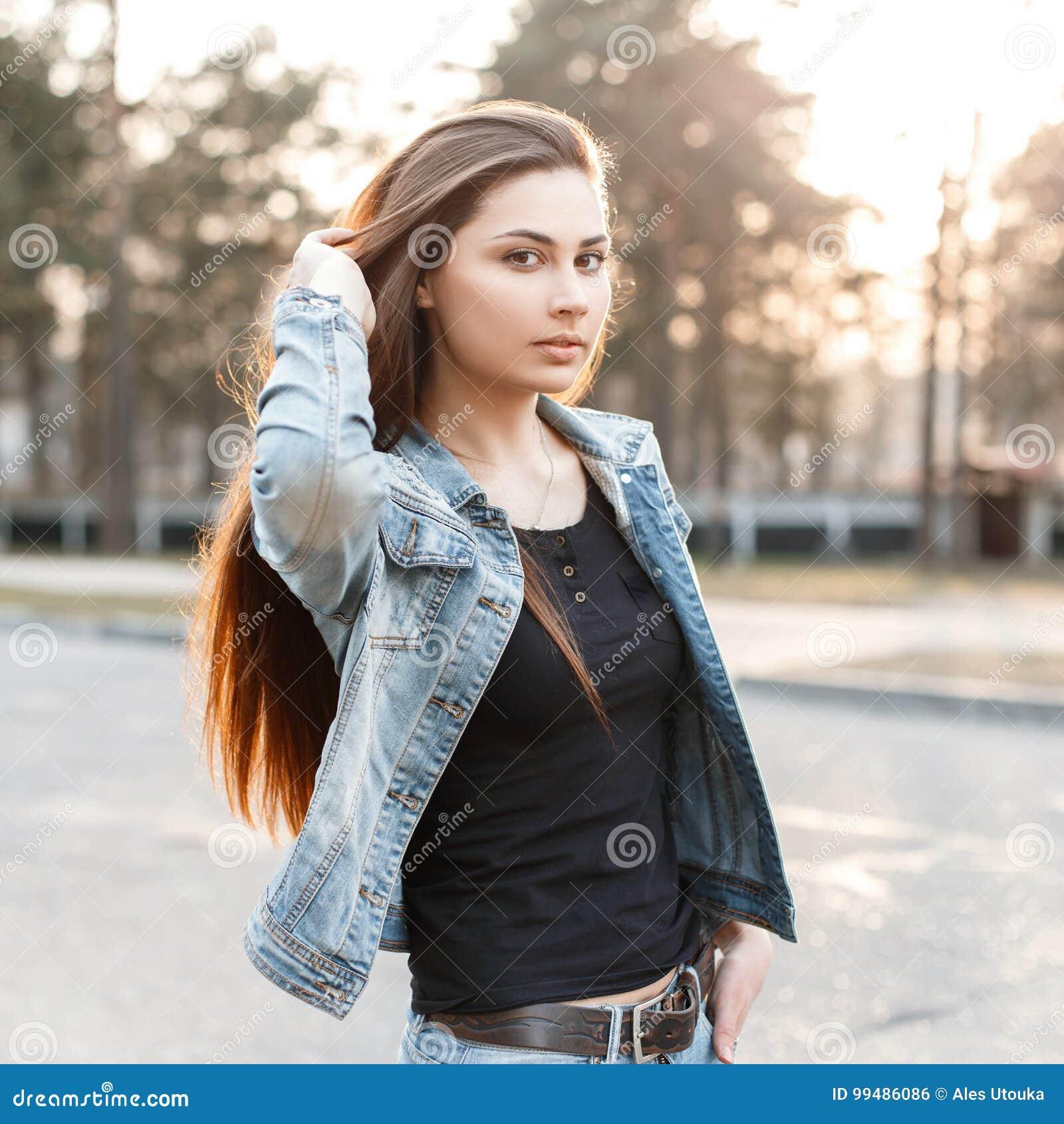 274791eeb91ae La jeune fille élégante dans des vêtements à la mode de jeans corrige ses  longs cheveux au coucher du soleil Mode de denim