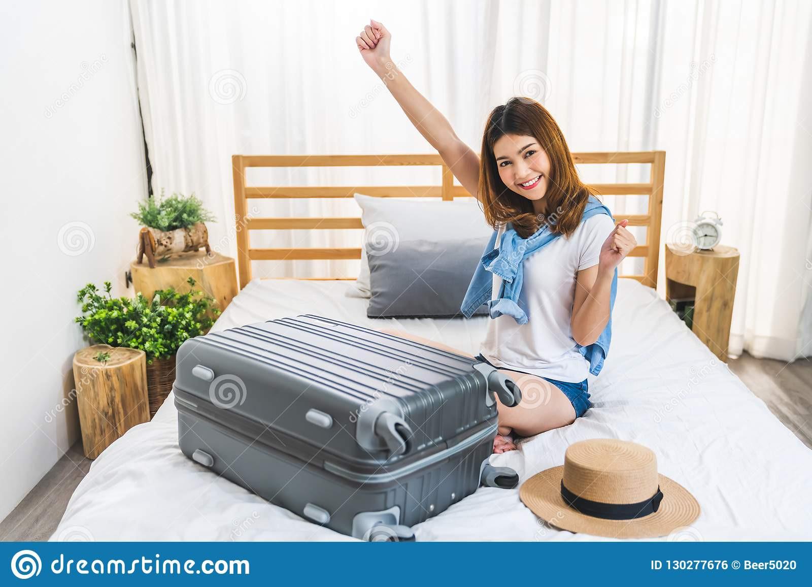 La jeune fille asiatique heureuse mignonne a fini d emballer le bagage de valise sur le lit dans la chambre à coucher, prête à al